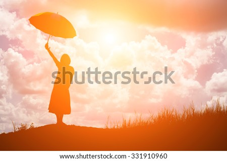 woman holding umbrella standing alone at the field during beautiful sunset - stock photo