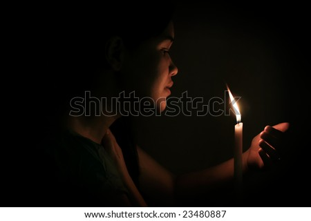 Woman holding up a candle and gazing into the light