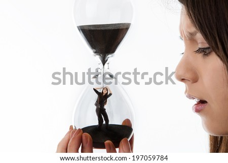 woman holding up a hour glass sand timer watching time slip away with herself inside the glass