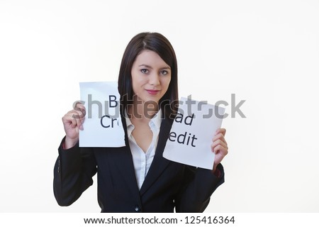 woman holding up a piece of paper with the words bad credit written on it and tearing the sheet of paper in half - stock photo