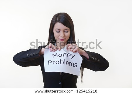 woman holding up a piece of paper with the words money problems written on it and tearing the sheet of paper in half - stock photo