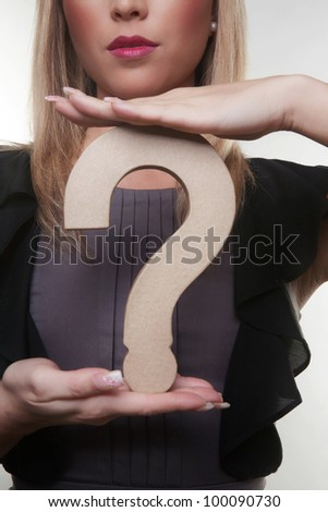 woman holding up a questions mark model to her chest