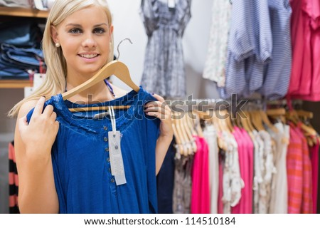 Woman holding up blue shirt and smiling in clothing store - stock photo