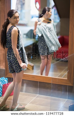 Woman holding up clothes and looking in the mirror in clothes store - stock photo