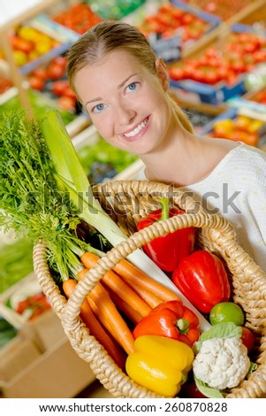 Woman holding up her shopping basket - stock photo