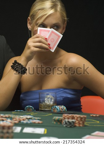 Woman holding up playing cards at poker game - stock photo