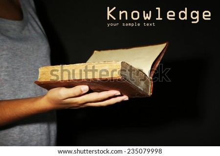 Woman holding very old book with dust, on dark background - stock photo