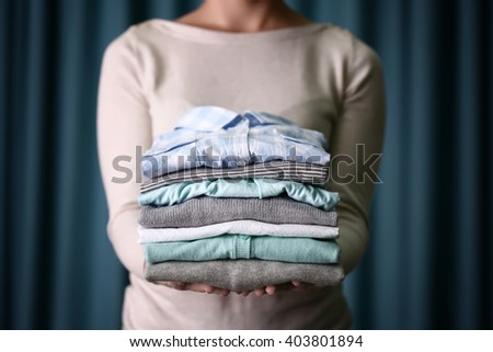 Woman holding washed and dried clothes on curtain background - stock photo