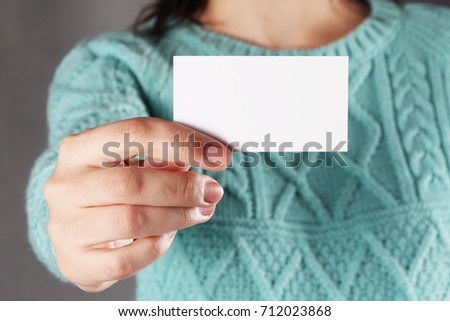 Woman holding white business card on gray wall background