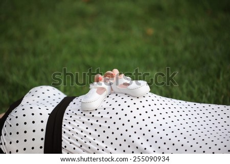 woman holding white kid's shoes on belly - stock photo