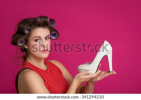 Woman holding white shoe happy sexy with copy space for text. Beautiful excited smiling joyful Caucasian female fashion model in red dress on pink background. Energetic - stock photo