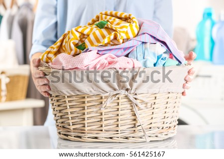 Woman holding wicker basket with clean clothes