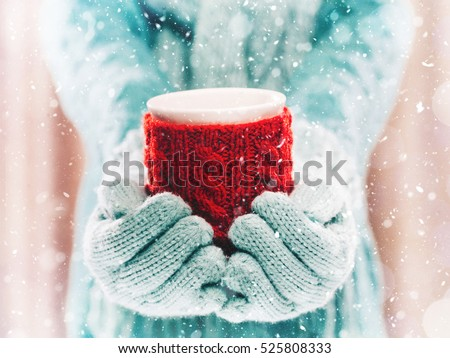 Woman holding winter cup close up on light background with snowfall. Woman hands in teal gloves holding a cozy mug with hot cocoa, tea or coffee and a candy cane. Winter and Christmas time concept