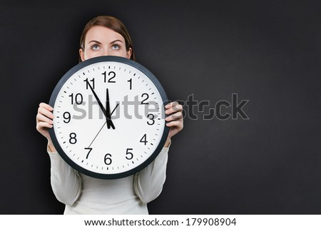 Woman holding with on office clock against bank chalkboard background - stock photo