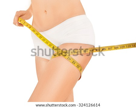 Woman holding yellow meter measuring perfect shape of her beautiful legs, with hands near waistline, on a white background