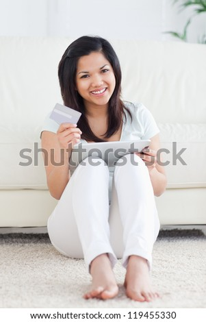 Woman holds a card and plays with a tactile tablet in a living room - stock photo