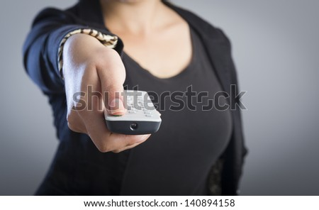 Woman holds a remote control in her hands with her body out of focus - stock photo