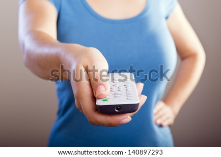 Woman holds a remote control in her hands with her body out of focus