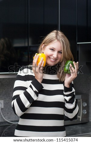 Woman holds a yellow and a green paprika in her hands while standing in the kitchen - stock photo