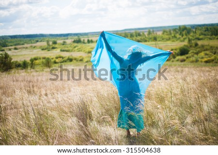 Woman holds blue shawl in field of wild grass field at sunset light Empty space for inscription Barefoot young adult girl keep in hands transparent cloth against meadow in perspective  - stock photo
