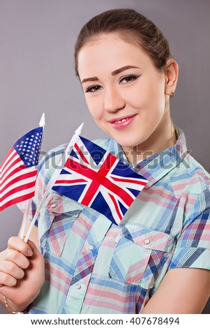 Woman holds british and american flag concept for learning english language  - stock photo