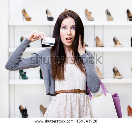 Woman holds credit card in footwear shop with great variety of stylish shoes - stock photo