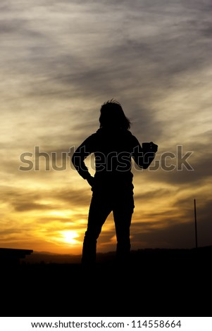 Woman holds cup at sunset. - stock photo