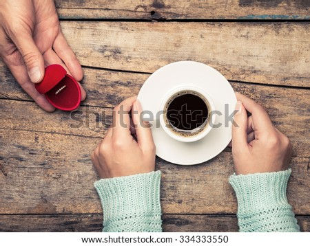 Woman holds cup of coffee and man gives gold ring as a gift for birthday or engagement - stock photo