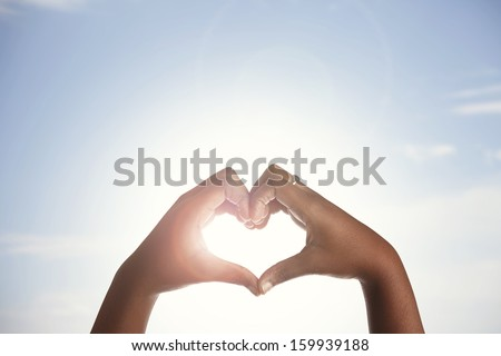 Woman holds hands up to sky in the shape of a heart around the sun.  - stock photo
