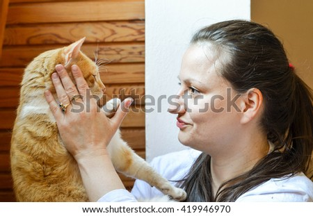 Woman holds her adorable cuddly cat - stock photo