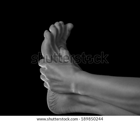 Woman holds her foot, pain in the foot, monochrome image - stock photo