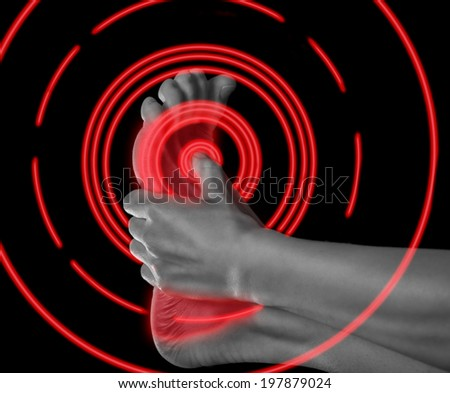 Woman holds her foot, pain in the foot, monochrome image, pain area of red color - stock photo