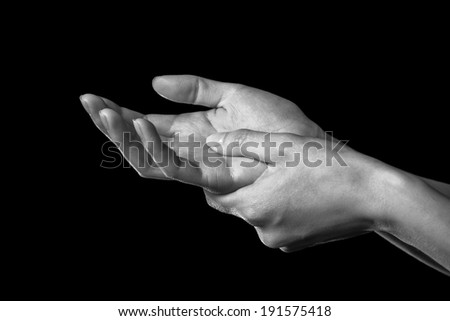 Woman holds her hand, pain in the wrist, black and white image