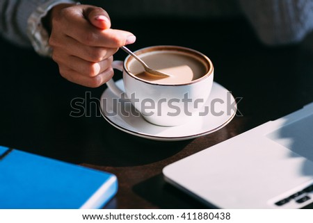 Woman holds hot cup of coffee, warming her hands - stock photo