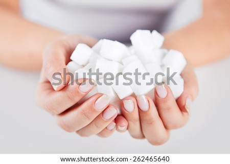Woman holds in hands of a handful of sugar cubes - stock photo