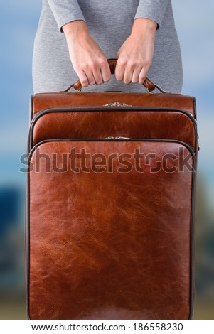 Woman holds leather suitcase with copy space - stock photo