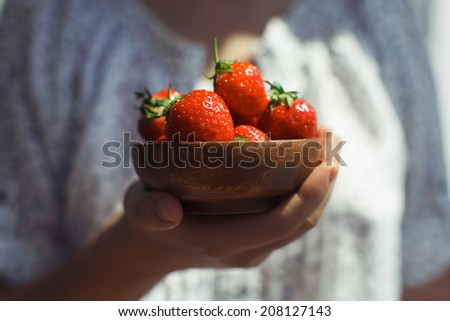 Woman holds plate of tasty strawberries
