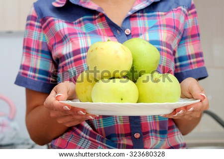 Woman holds plate with fresh green apples - stock photo