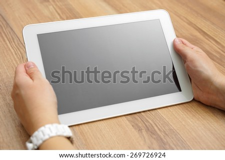 woman holds tablet computer  on desk with empty screen