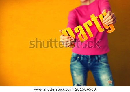 Woman holds word Party on bright colorful background - stock photo