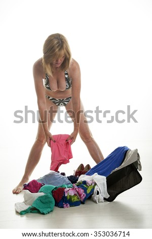 Woman holidaymaker wearing a bikini packing a suitcase