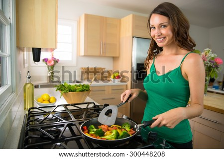 Woman home chef single portrait cooking vegetables vegan meal on stove grill - stock photo