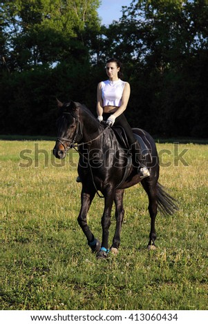 Woman horseback riding in evening rural field - stock photo