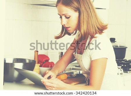 woman housewife cooks food a recipe from the Internet with a tablet computer  in the kitchen  - stock photo