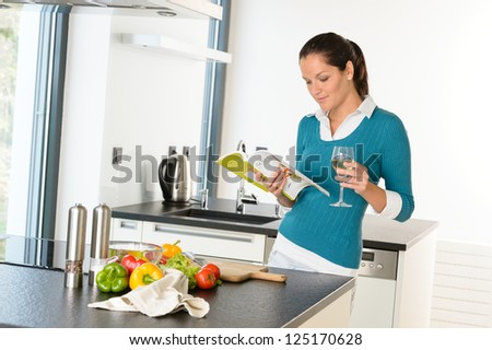 Woman housewife reading cooking book recipe kitchen wine vegetables - stock photo
