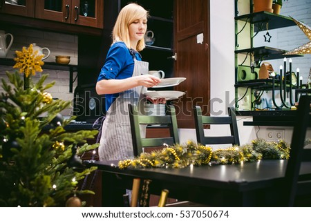 woman housewife setting the table. young blonde in a dress and apron, served in a dining table, puts the dishes, doing the work in the kitchen
