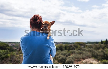 woman hugging a dog and watching a beautiful landscape - stock photo