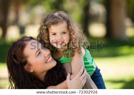 Woman hugging her daughter in the park - stock photo