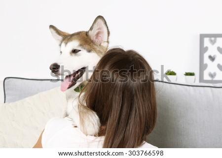 Woman hugging malamute dog in room - stock photo