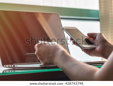Woman human hand holding credit card smart phone using pc laptop computer wifi wireless internet IT IOT PPC market shopping advertising: Office buyer customer typing credit card number goods/ booking  - stock photo
